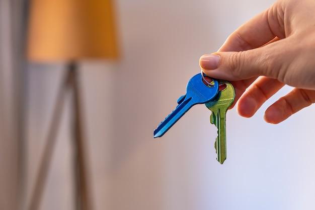 Mão segurando as chaves com o quarto na superfície aluguel vender comprar apartamento negócio imobiliário