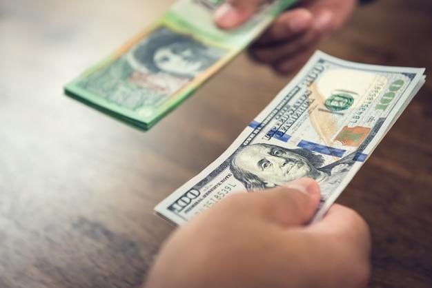 Mão segurando as notas de dólar nos negócios com dólares australianos