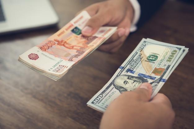 Mão segurando as notas de dólar nos negócios com moeda do rublo russo