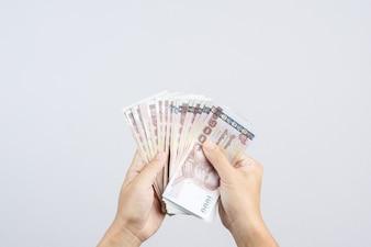 Mão segurando as notas tailandesas de moeda de 1000 baht ou dinheiro na Tailândia