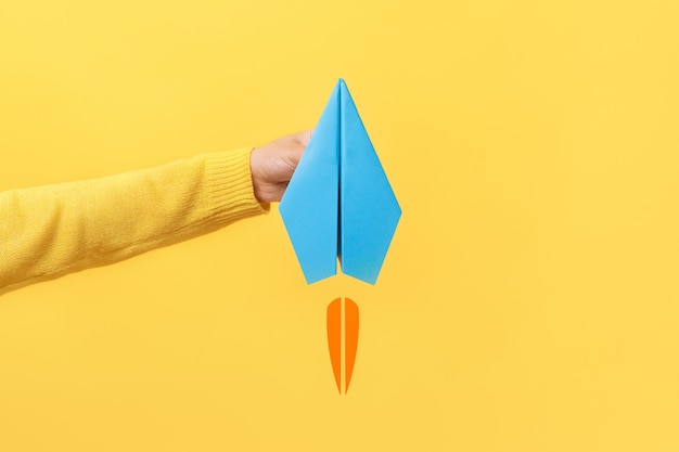 Mão segurando avião de papel
