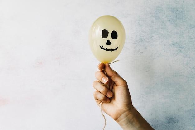 Mão segurando balão branco com cara assustadora