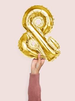 Mão segurando balão e símbolo &