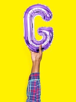 Mão segurando balão letra g