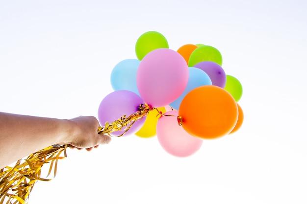 Mão segurando balões multicoloridos