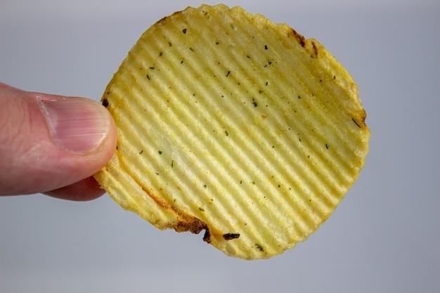 Mão segurando batatas fritas isoladas em branco.