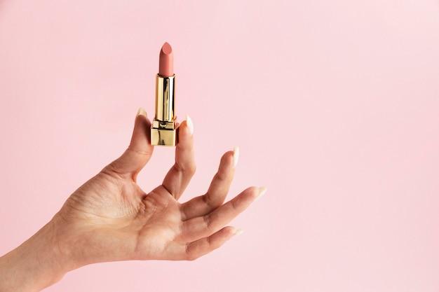 Mão segurando batom rosa de perto