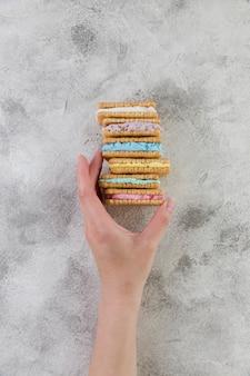 Mão segurando biscoitos com sorvete no fundo cinza