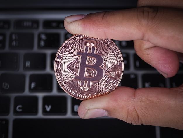 Mão segurando bitcoin com computador portátil