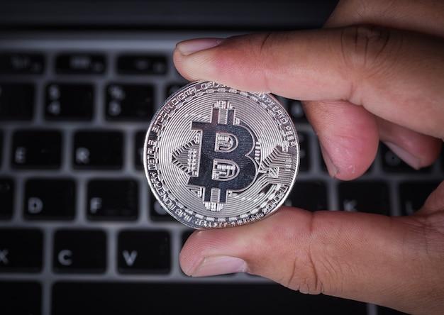 Mão segurando bitcoin prata com computador portátil