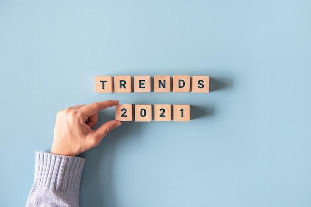 Mão segurando blocos de madeira com a palavra tendências do ano
