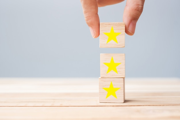 Mão segurando blocos de madeira com o símbolo da estrela. críticas de clientes, feedback, classificação, classificação e conceito de serviço.
