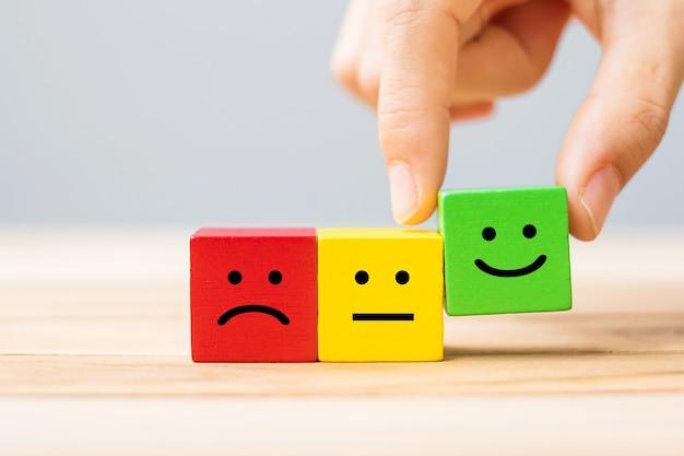 Mão segurando blocos de madeira de símbolo de rosto emocional
