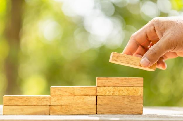 Mão segurando blocos de madeira para fazer a etapa crescer verde borrão com espaço da cópia para o conceito de texto ou design para o conceito de negócio
