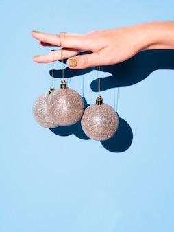 Mão segurando bolas de decoração