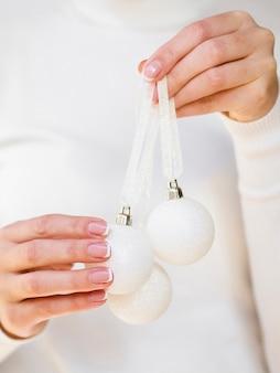 Mão segurando bolas de natal branco