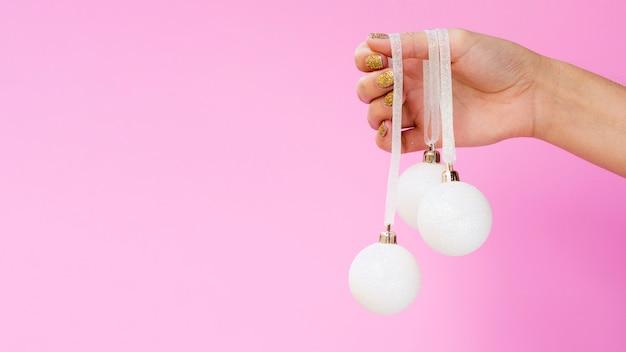 Mão segurando bolas de natal com espaço de cópia
