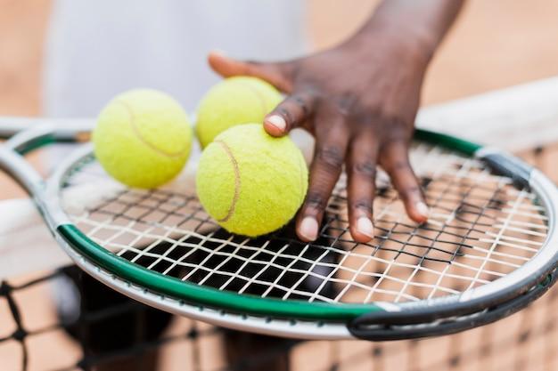 Mão segurando bolas e raquete de tênis
