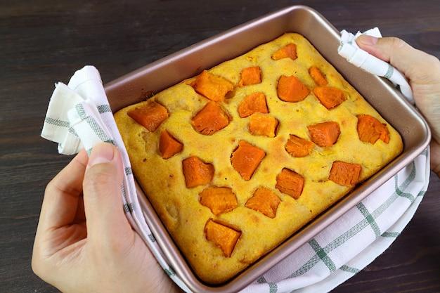 Mão segurando bolo fresco de abóbora assado com pano de cozinha e colocando na mesa de madeira