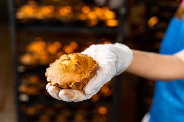 Mão segurando bolo ou bolinho. fundo do forno de fábrica.