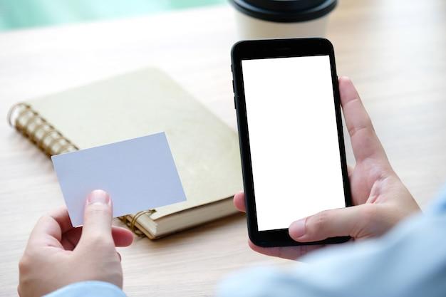 Mão segurando businesscard branco em branco e smartphone com fundo de tela do dispositivo em branco