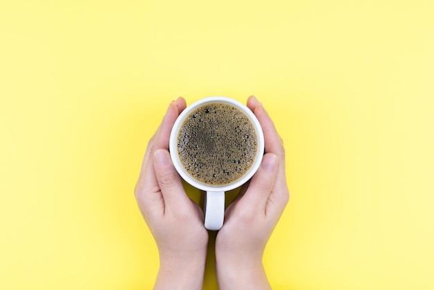Mão segurando café americano e xícara branca