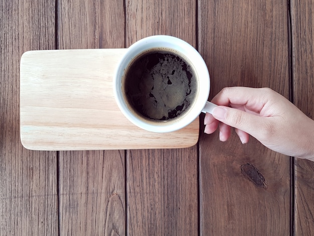 Mão segurando café preto na mesa de madeira, tiro horizontal