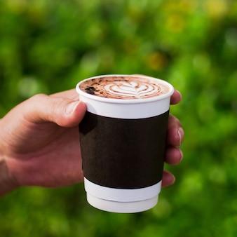 Mão segurando café quente latte takeaway copo na natureza verde bokeh