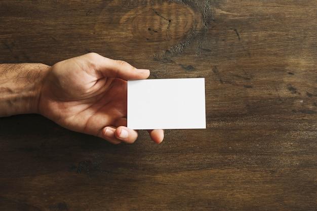 Mão segurando cartão em branco