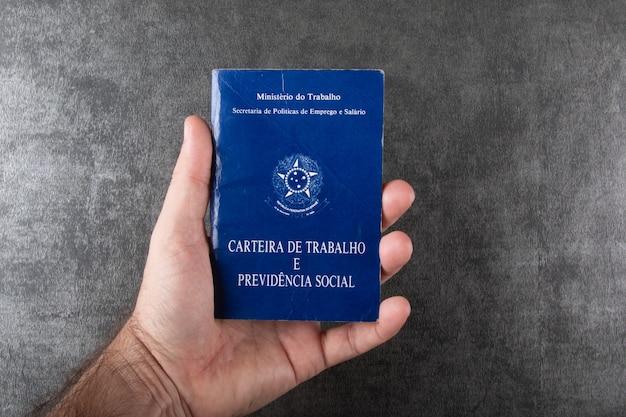 Mão segurando carteira de trabalho brasileira
