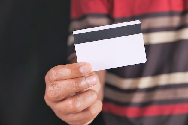 Mão segurando cartões de crédito, lendo informações.