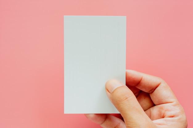 Mão segurando cartões em branco sobre fundo rosa