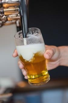 Mão segurando cerveja de enchimento de vidro