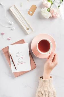 Mão segurando chá bebida plana leigos