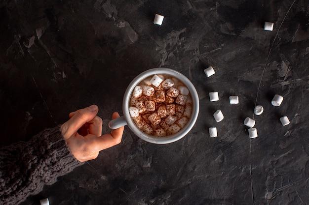 Mão segurando chocolate quente com marshmallows e cacau em pó