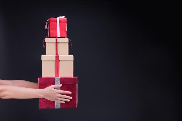 Mão segurando com muitas caixas de presente do feliz natal e feliz ano novo preto