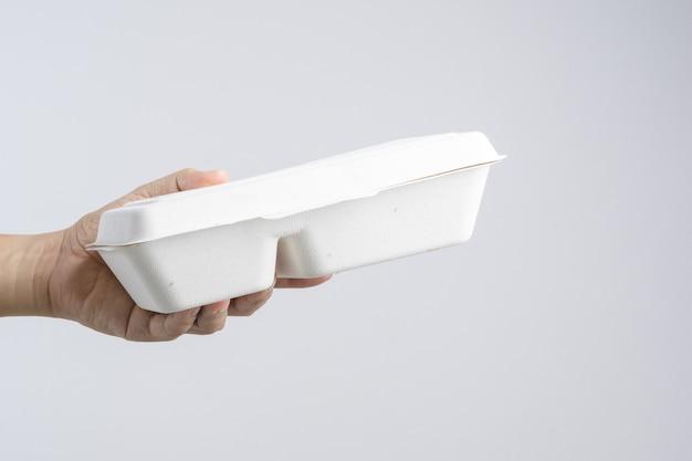 Mão segurando comida tailandesa na caixa de comida de papel de fibra vegetal
