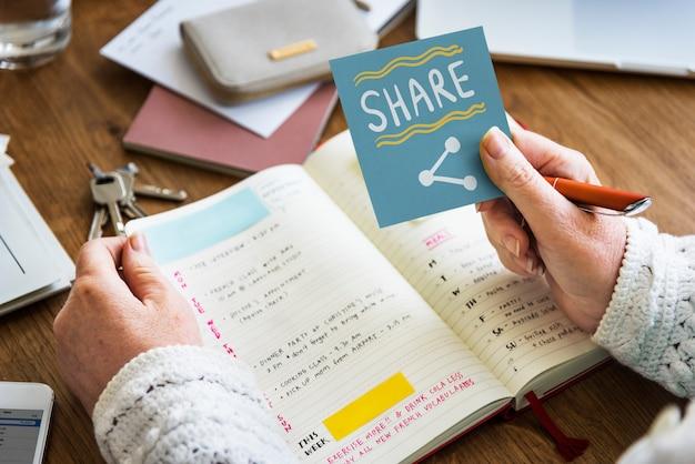 Mão segurando compartilhar em uma nota auto-adesiva