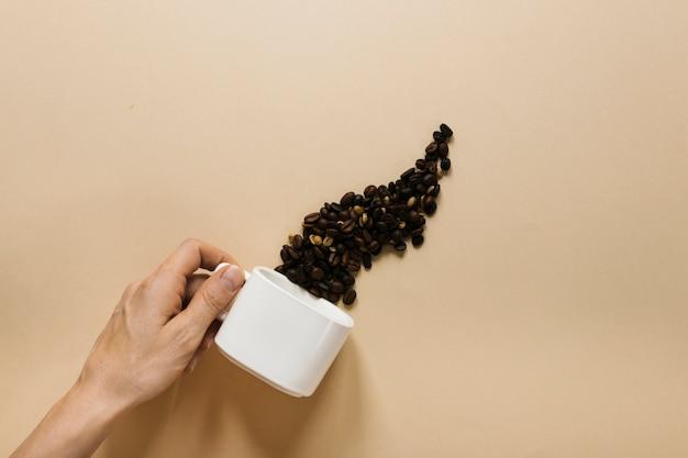 Mão segurando copo branco com grãos de café