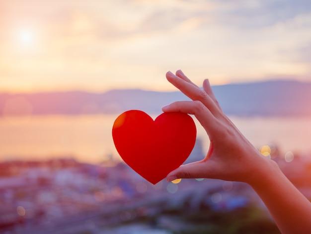 Mão segurando coração vermelho durante o fundo por do sol. amor, conceito de dia dos namorados.