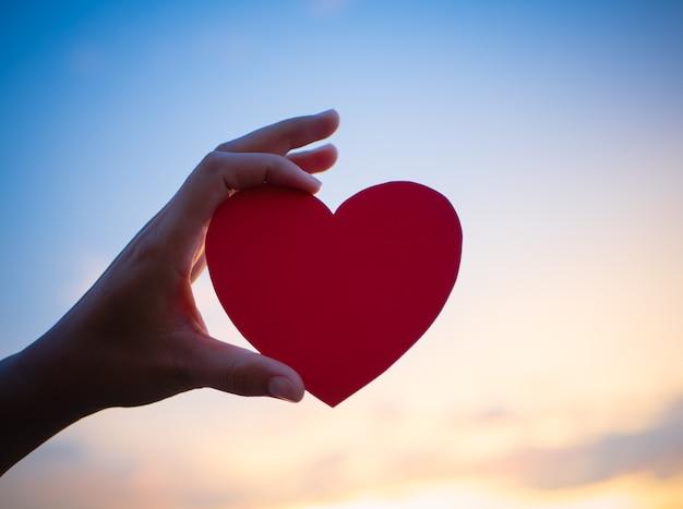 Mão segurando coração vermelho durante o fundo por do sol.