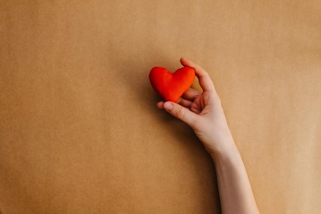 Mão segurando coração vermelho feito à mão.