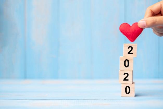 Mão segurando coração vermelho sobre blocos de 2020