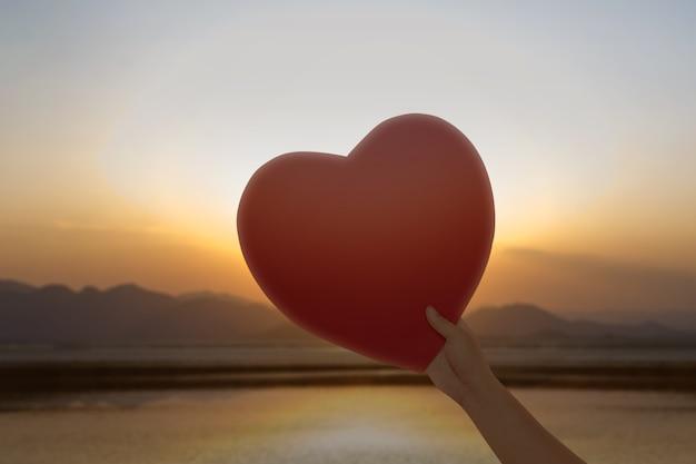 Mão segurando corações vermelhos com um fundo do céu do sol. dia dos namorados