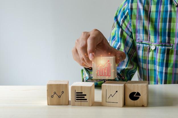 Mão segurando cubos ícones do gráfico de negócios