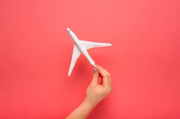 Mão segurando cuidadosamente o avião modelo. avião em fundo de cor rosa.