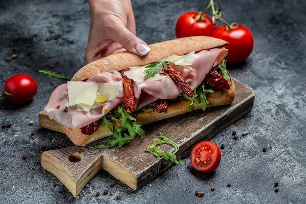 Mão segurando deliciosos sanduíches submarinos com presunto, queijo, bacon, tomate, alface. banner, menu, lugar de receita para texto.