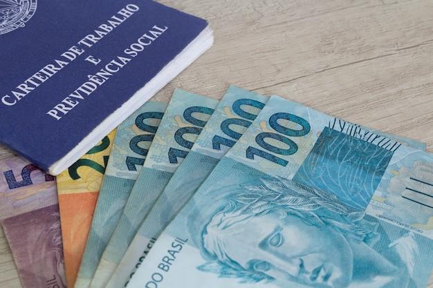 Mão segurando dinheiro brasileiro e carteira de trabalho foco seletivo