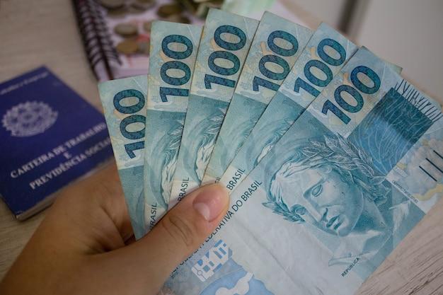 Mão segurando dinheiro brasileiro e carteira de trabalho