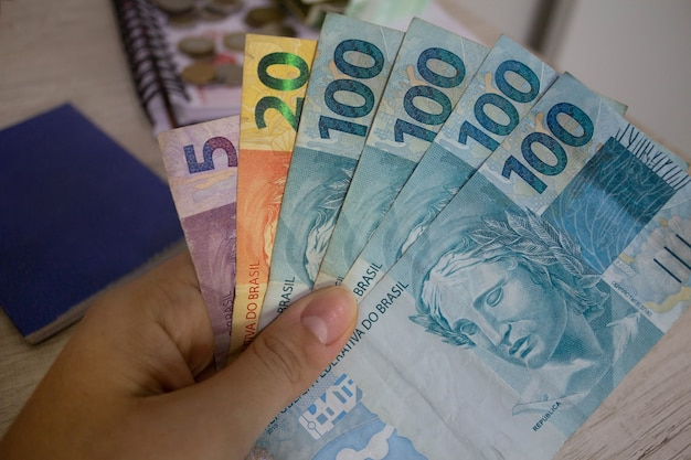 Mão segurando dinheiro brasileiro